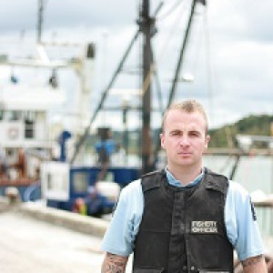 Kyall - Fisheries officer in uniform standing on a wharf