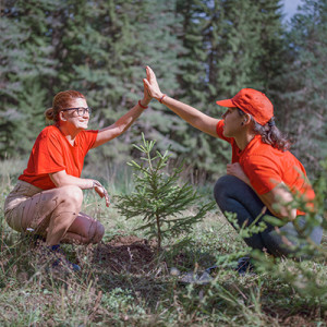 2 girls are giving each other high five after they plant a tree400x400