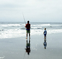 adult and child fishing on a beach
