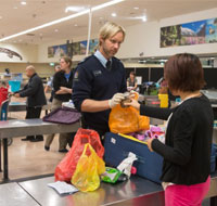 officer checking bags at Auckland airport