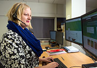 MPI employee wearing headset looking at computer