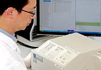 Scientist analysing real-time PCR data on a monitor next to PCR machine