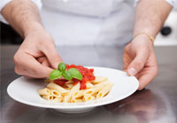 chef adding basil leaf to tomatoes on plate of pasta