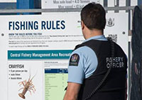 fisheries officer next to fishing rules sign