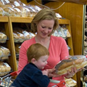 mother and son reading label on back of packaged loaf of bread