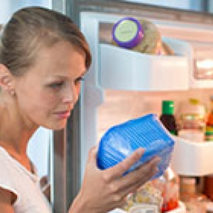 woman looking at product from refrigerator