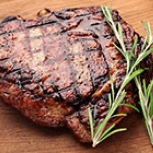 steak with rosemary on a wooden cutting board