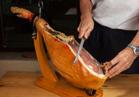 Man slicing serrano ham