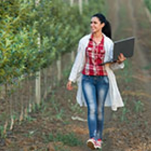 young woman in lab coat carrying laptop through an orchard